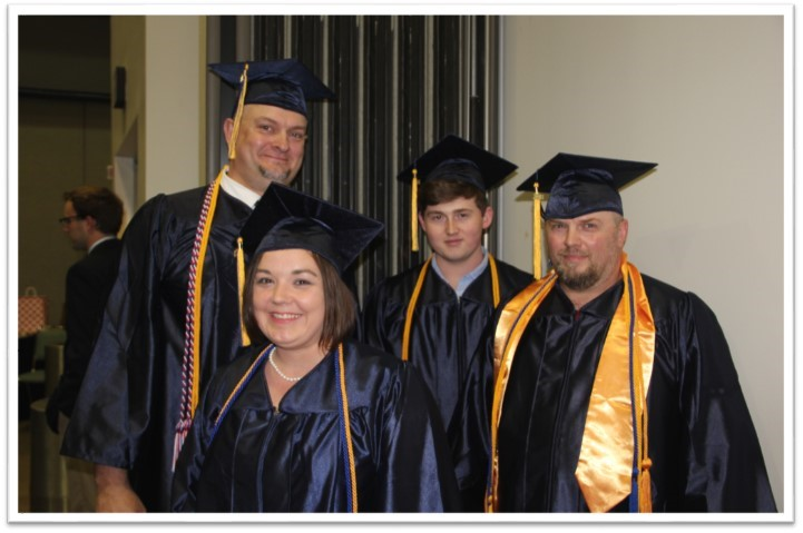 a group of four graduates smile happily in line up