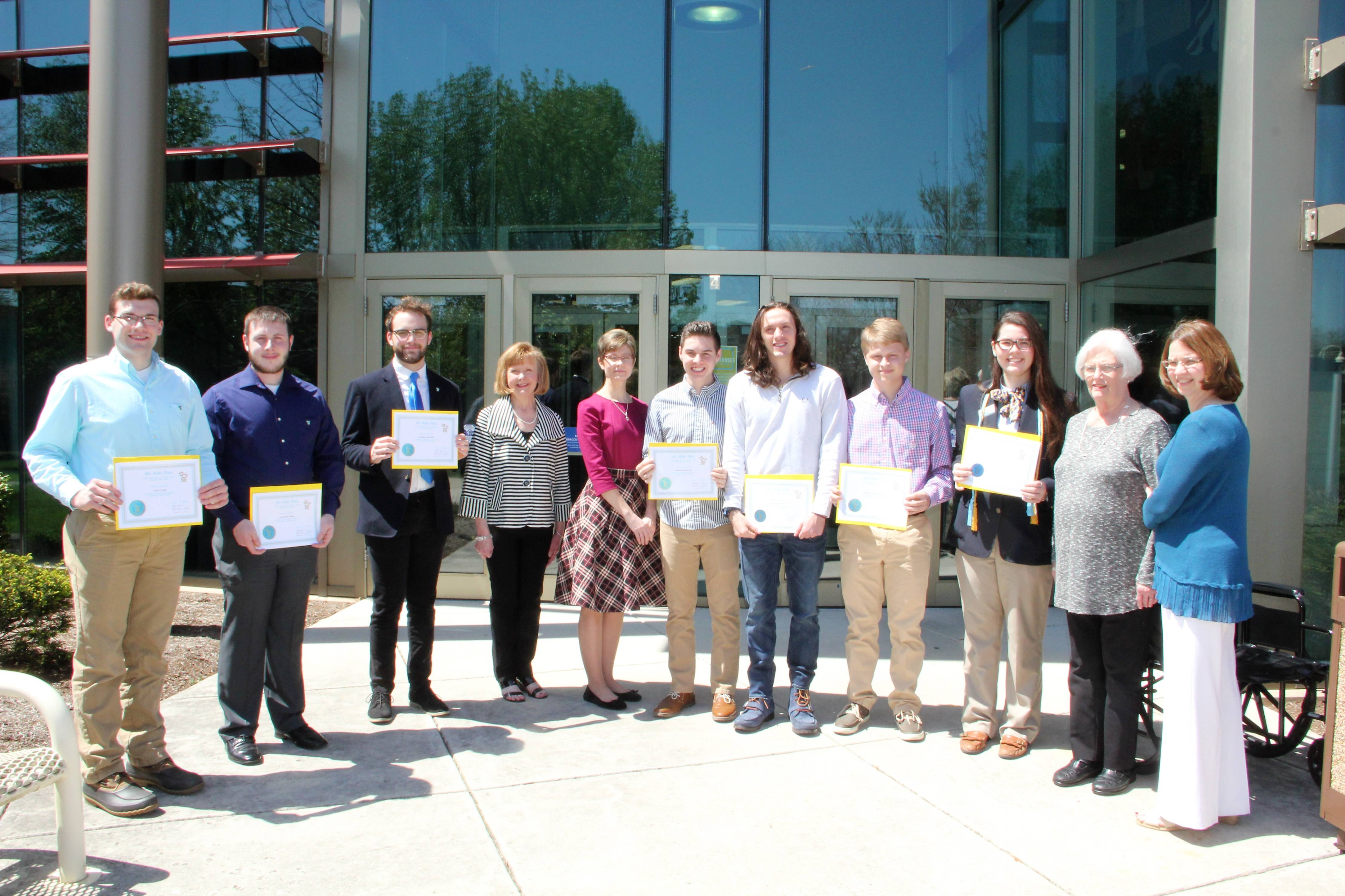 mu alpha theta inducted students standing outside of scc building holding up certificates