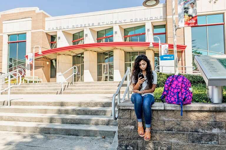 Female student in sitting outside scc building