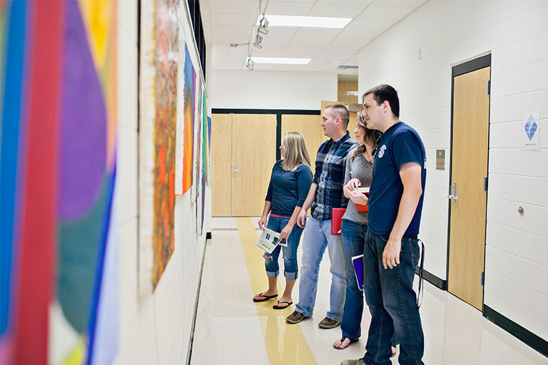 a group of students looking at paintings on the wall