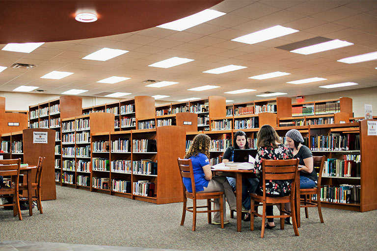 group of students studying at a table in the learning commons