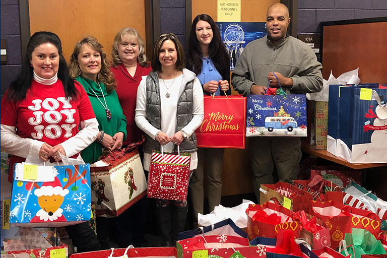 staff holding gifts for angel tree children