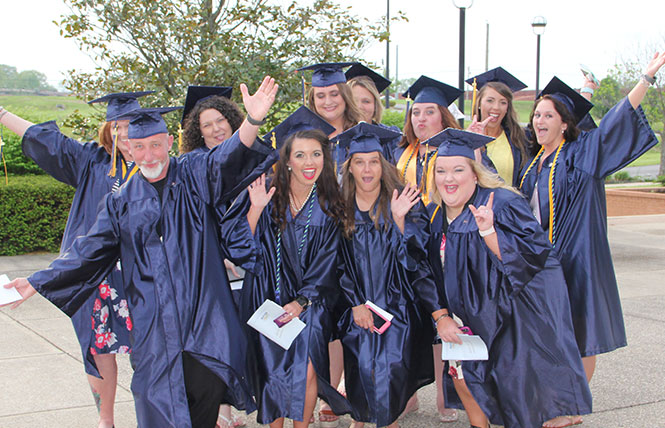 graduates pose happily outside before commencement