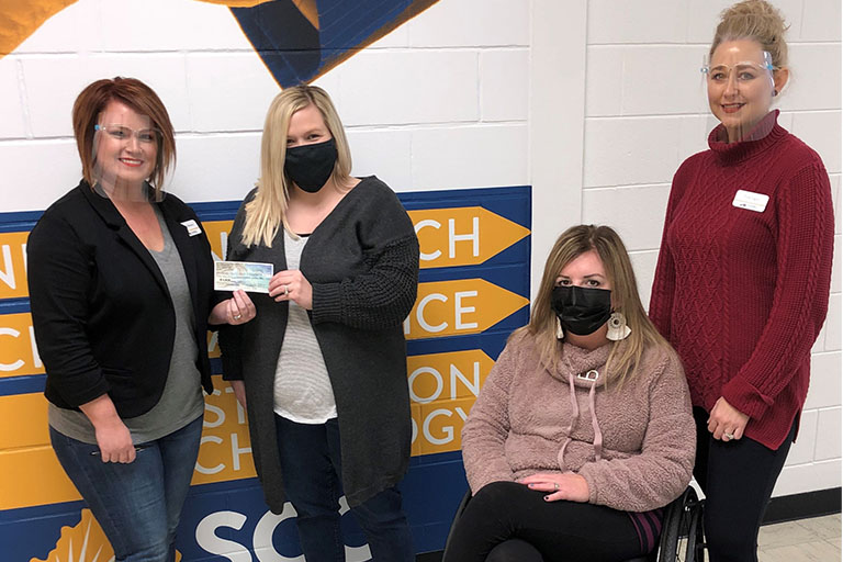 cosmetology professors on the laurel campus wearing masks holding check of donations