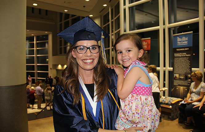 elated mother graduate holding daughter after commencement ceremony