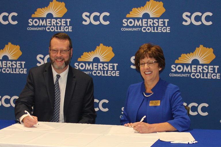 dr. Hayes and lindsey wilson signing a partnership for the honors program