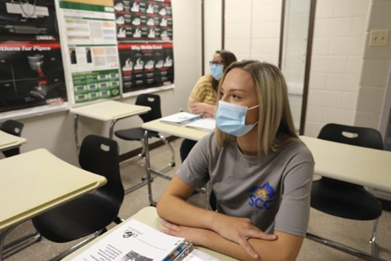 female student in class wearing a mask