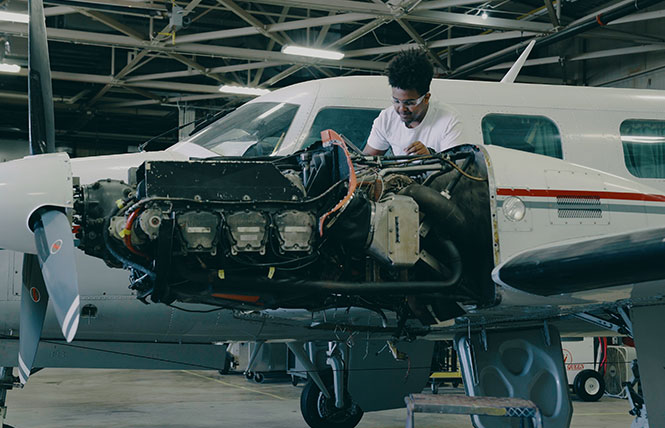 aviation student working on an airplane